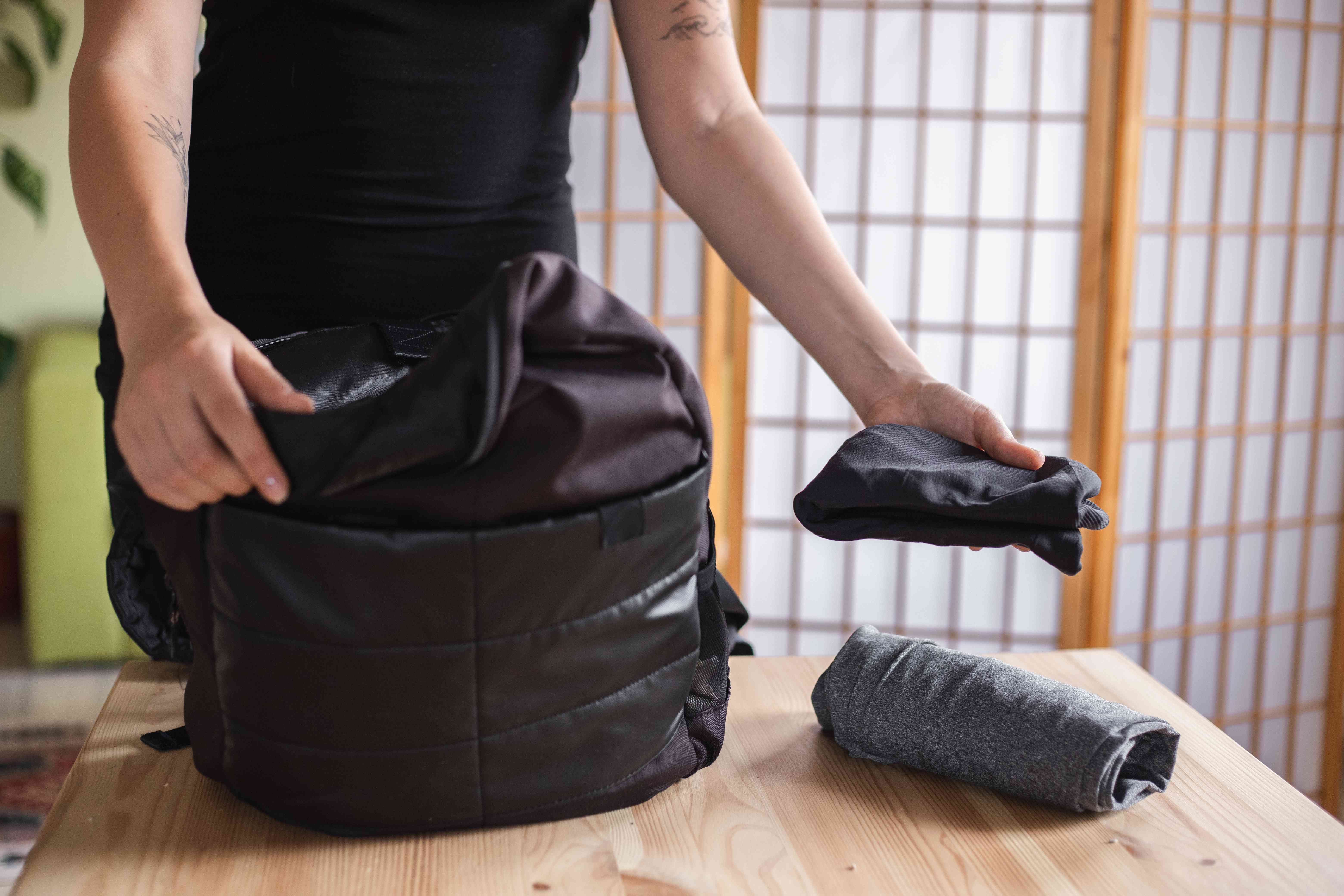 person pulls out workout clothes from a black backpack on puts on table