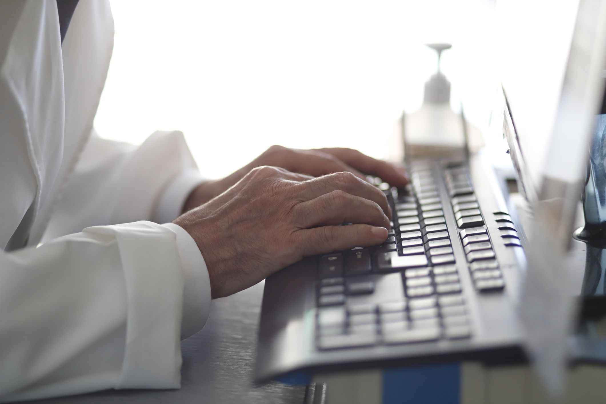 Detailed shot of person in a lab coat's hands typing on a computer.