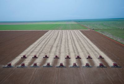 Rows of combines harvest soybeans at a farm in Mato Grosso, Brazil with green fields on the periphery.