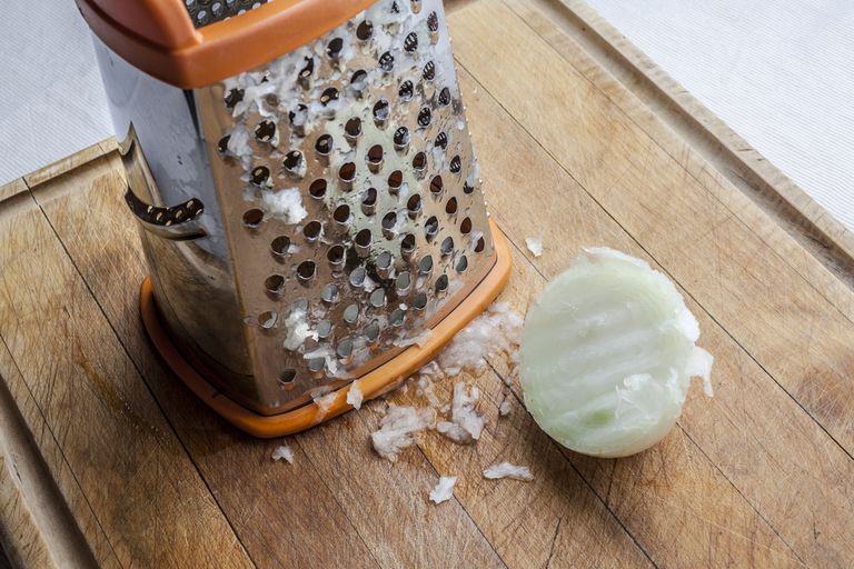 box grater and half an onion on a wood cutting board