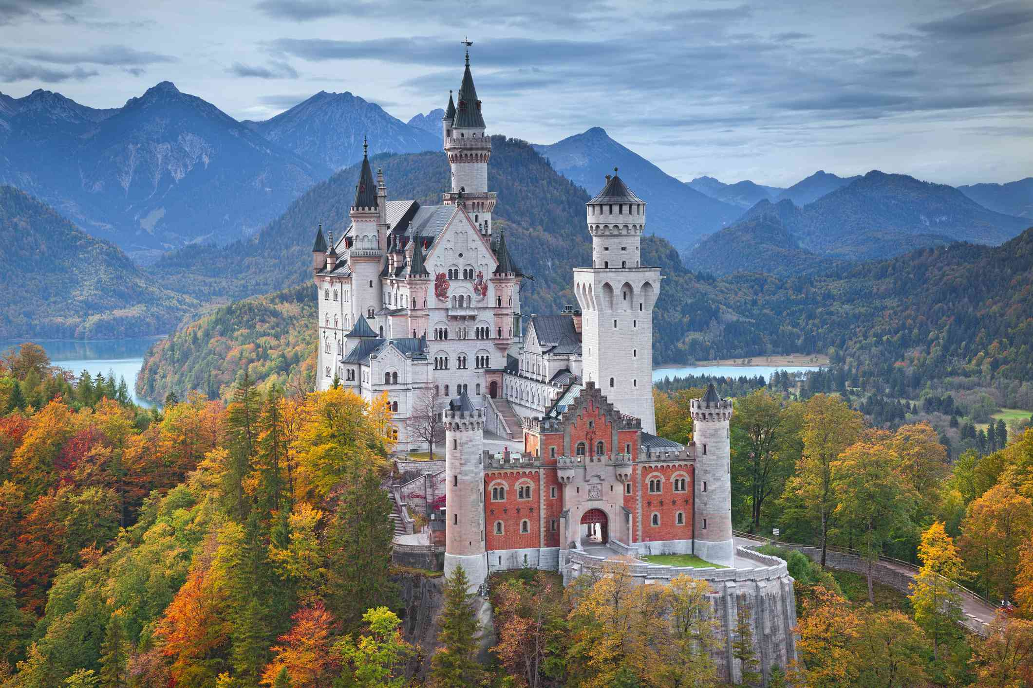 Aerial view of Neuschwanstein Castle surrounded by trees in shades of red, orange, green, and gold during autumn with mountain peaks and blue skies in the distance