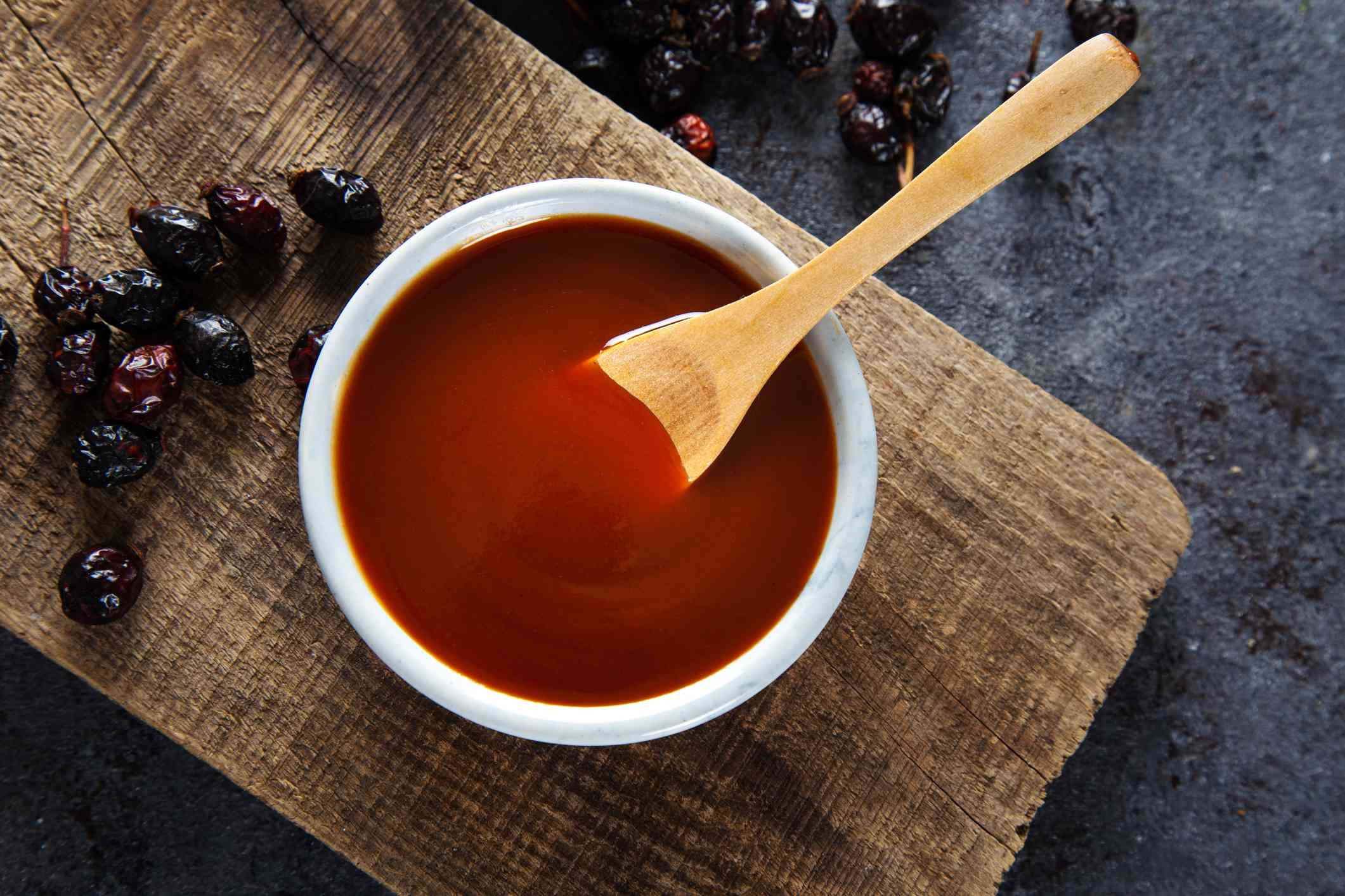 Homemade rosehip marmalade in ceramic bowl with dried rose hip fruits on wooden board.