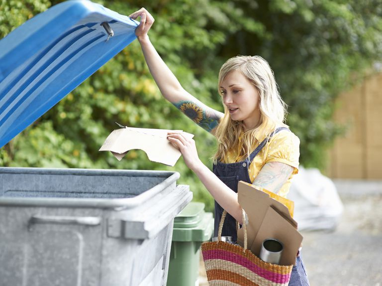 Young woman putting cardboard into recycling bin