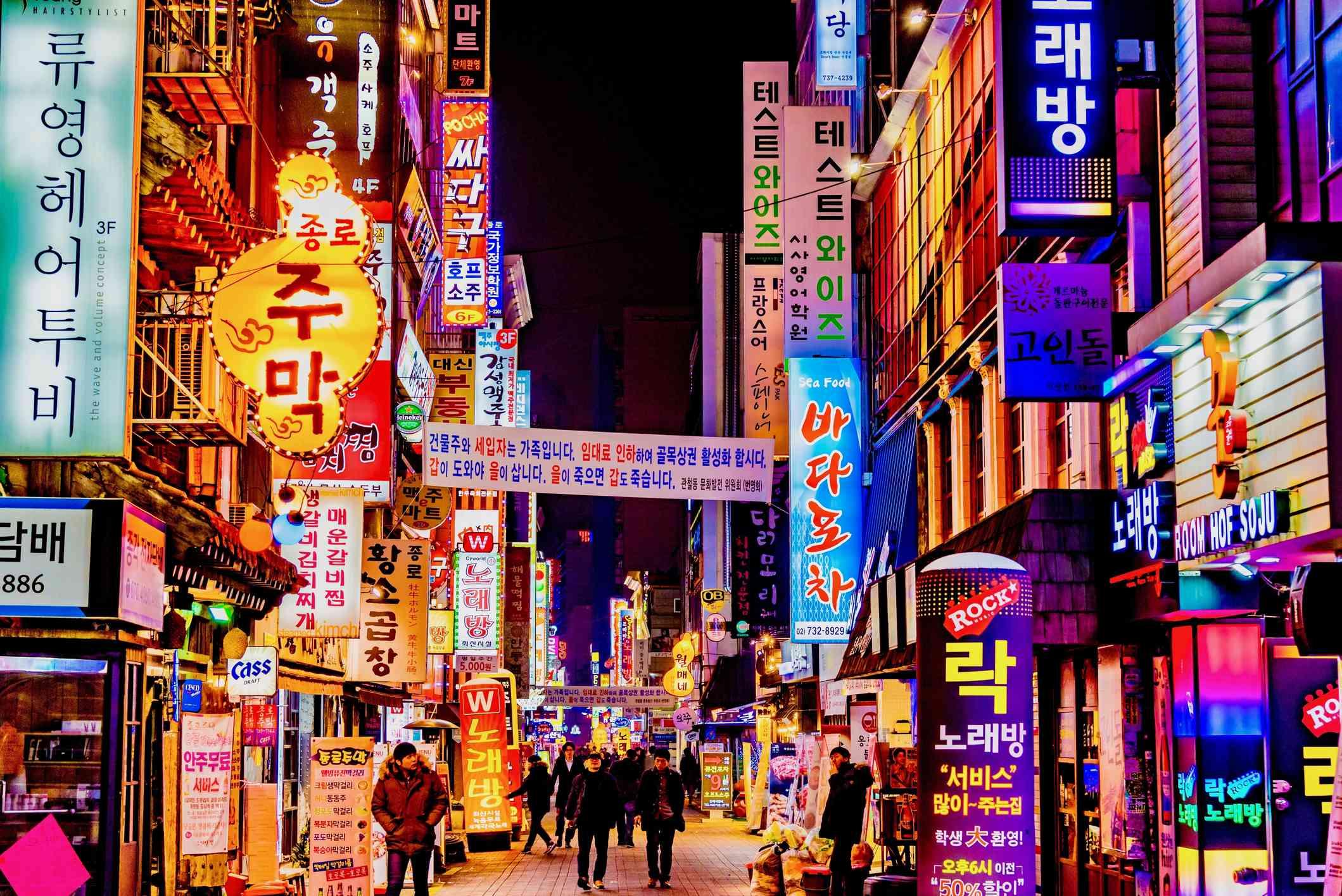 People walking between neon-lit buildings at night