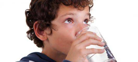 A young boy drinking water.