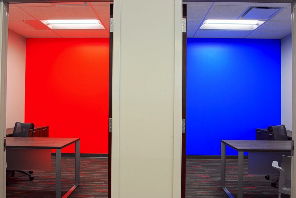Two offices, one with a red wall and one with a blue wall