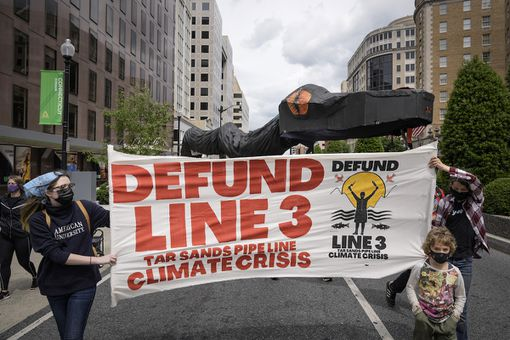 Environmental activists carry a large snake pipeline as they protest against the Enbridge Line 3 oil pipeline on May 7, 2021 in Washington, DC.
