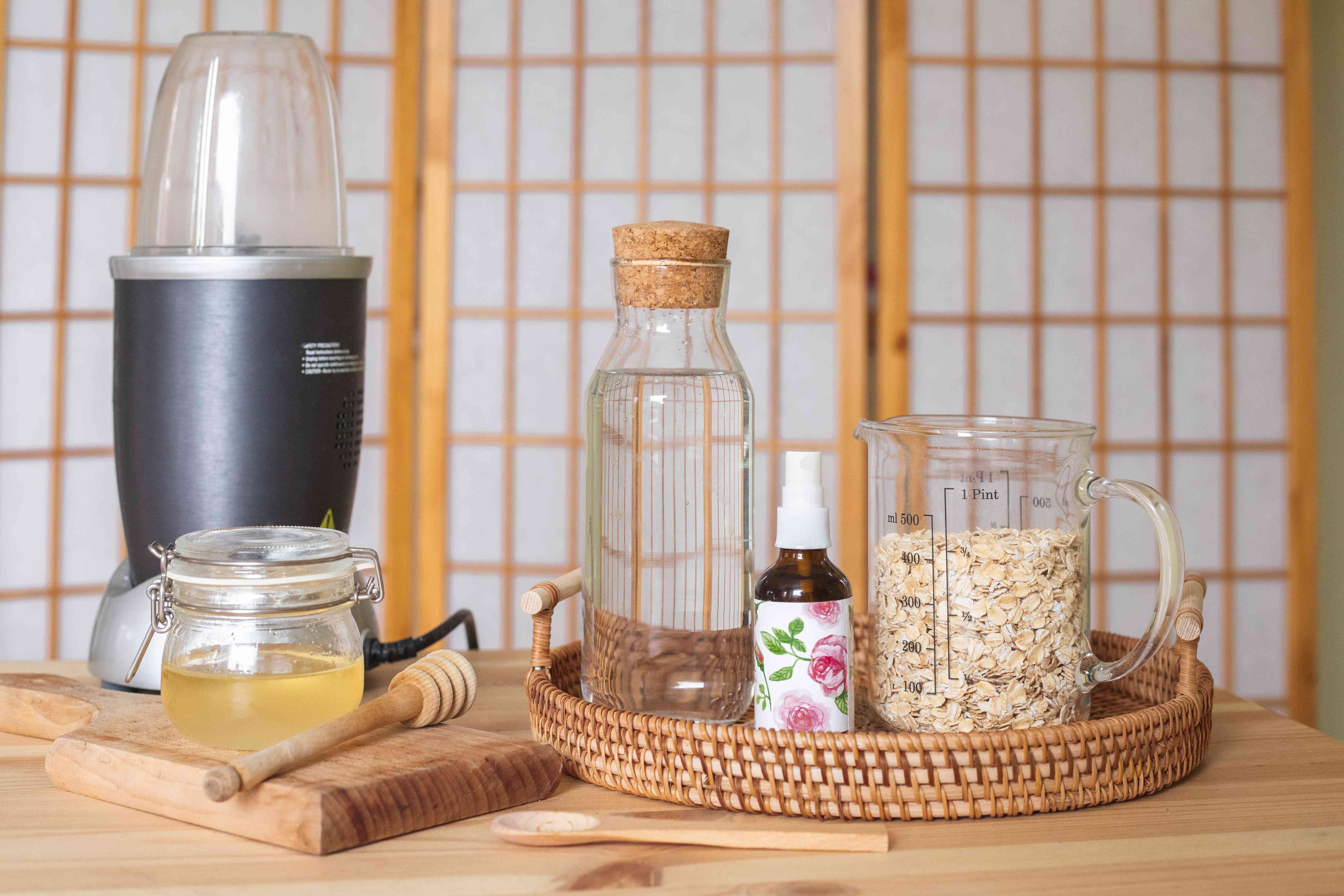 DIY setup for colloidal oatmeal including blender, honey, rosewater, and rolled oats