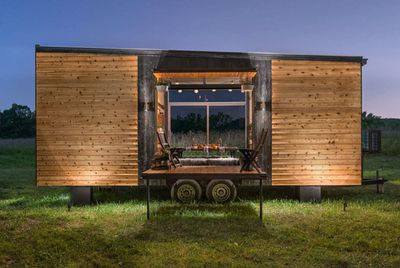 Tiny home exterior with open side garage-type door and fold out porch