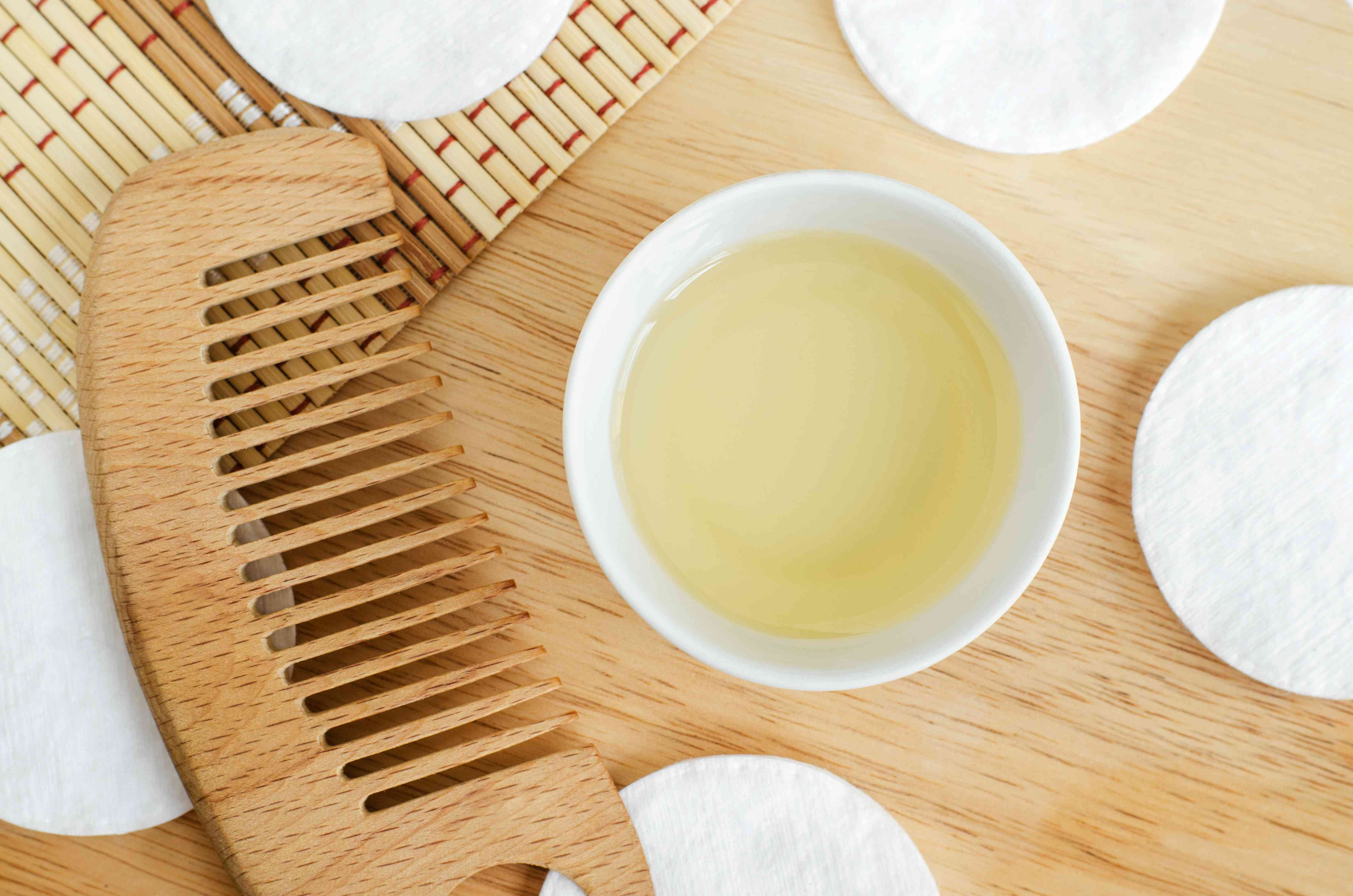 Olive oil, cotton pads and wooden hairbrush. Ingredients for preparing homemade hair mask. Natural beauty treatment recipe and zero waste concept. Top view, copy space.