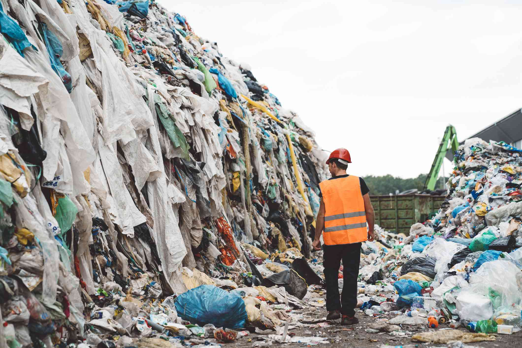 Worker walking through mounds of textile waste