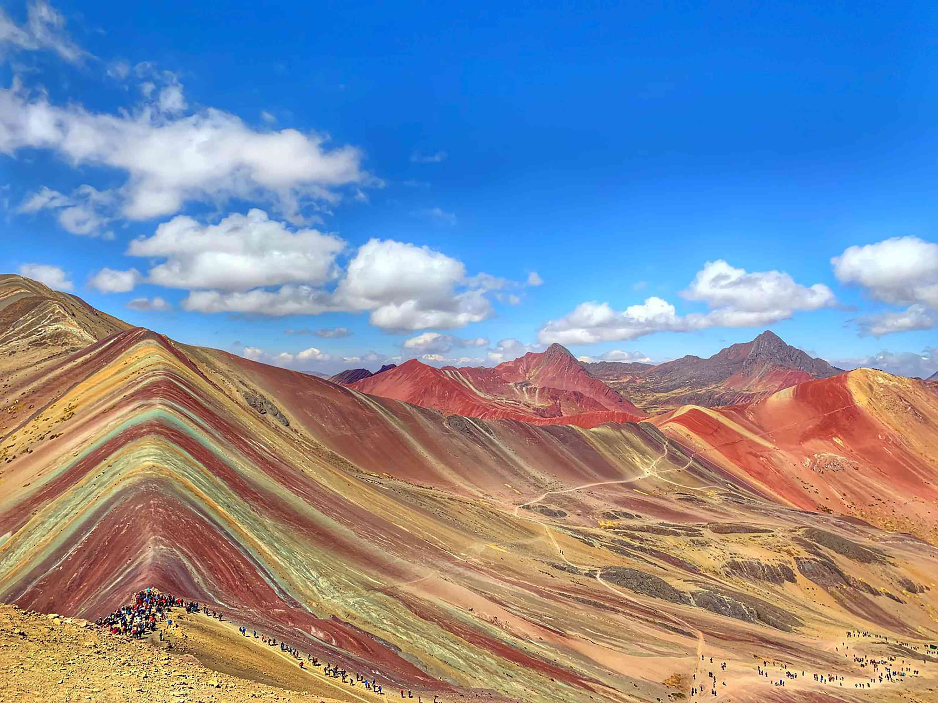 A multicolored mountain ridge on a sunny day with a line of tourists on a hiking trail