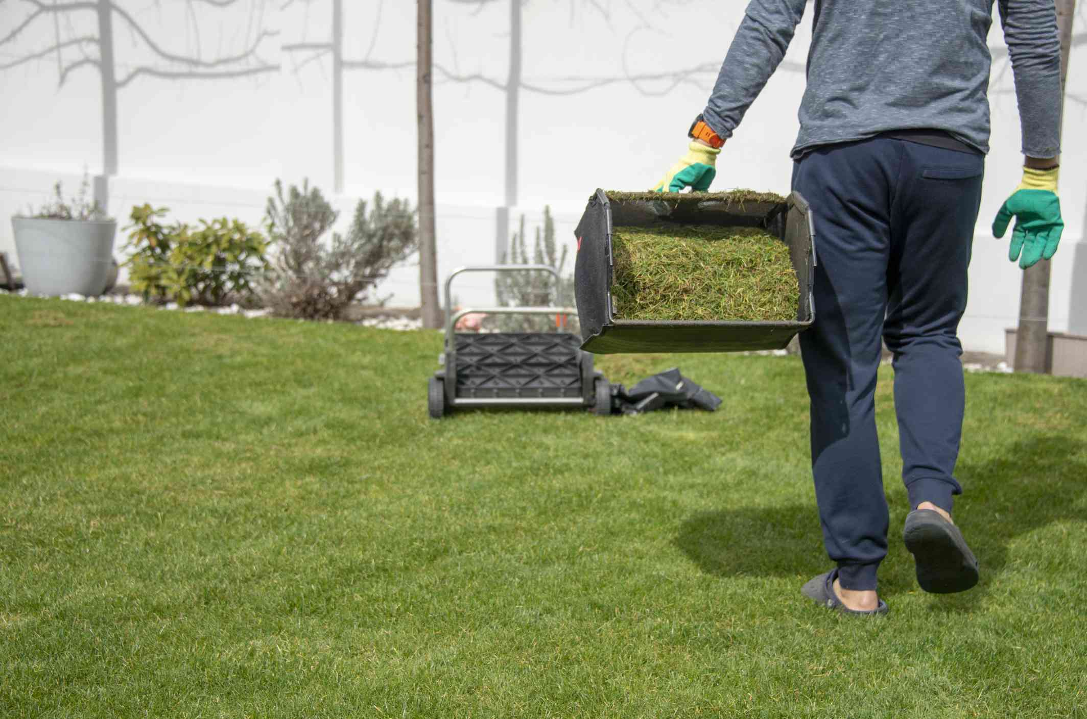 A man carrying part of lawn mower over cut grass.