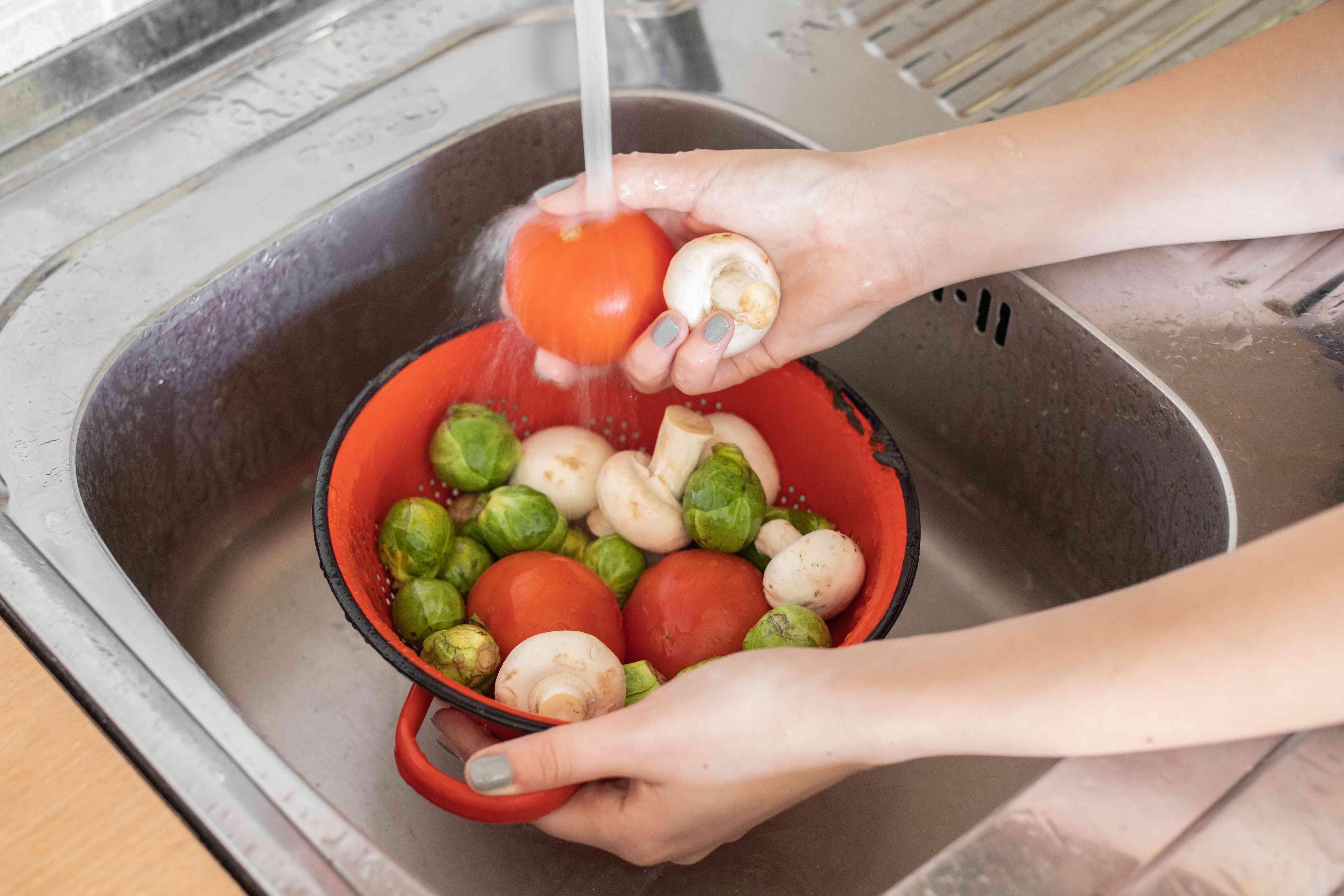 hands wash bowl of veggies with water in steel sink