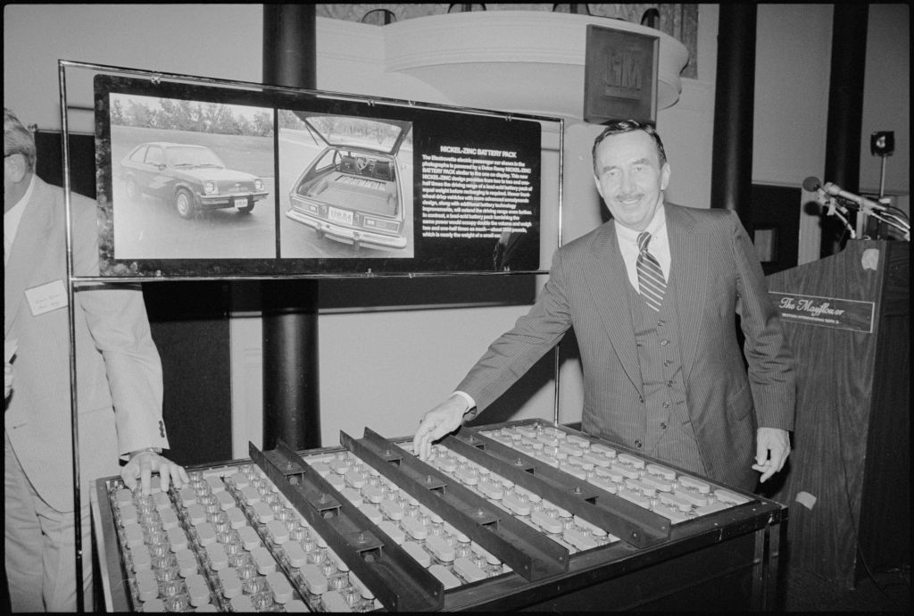 An unidentified General Motors employee smiles as he gestures to the battery pack for the concept car, the Chevrolet Electrovette.