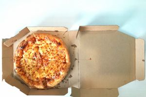 overhead shot of greasy pizza in cardboard box with grease stains