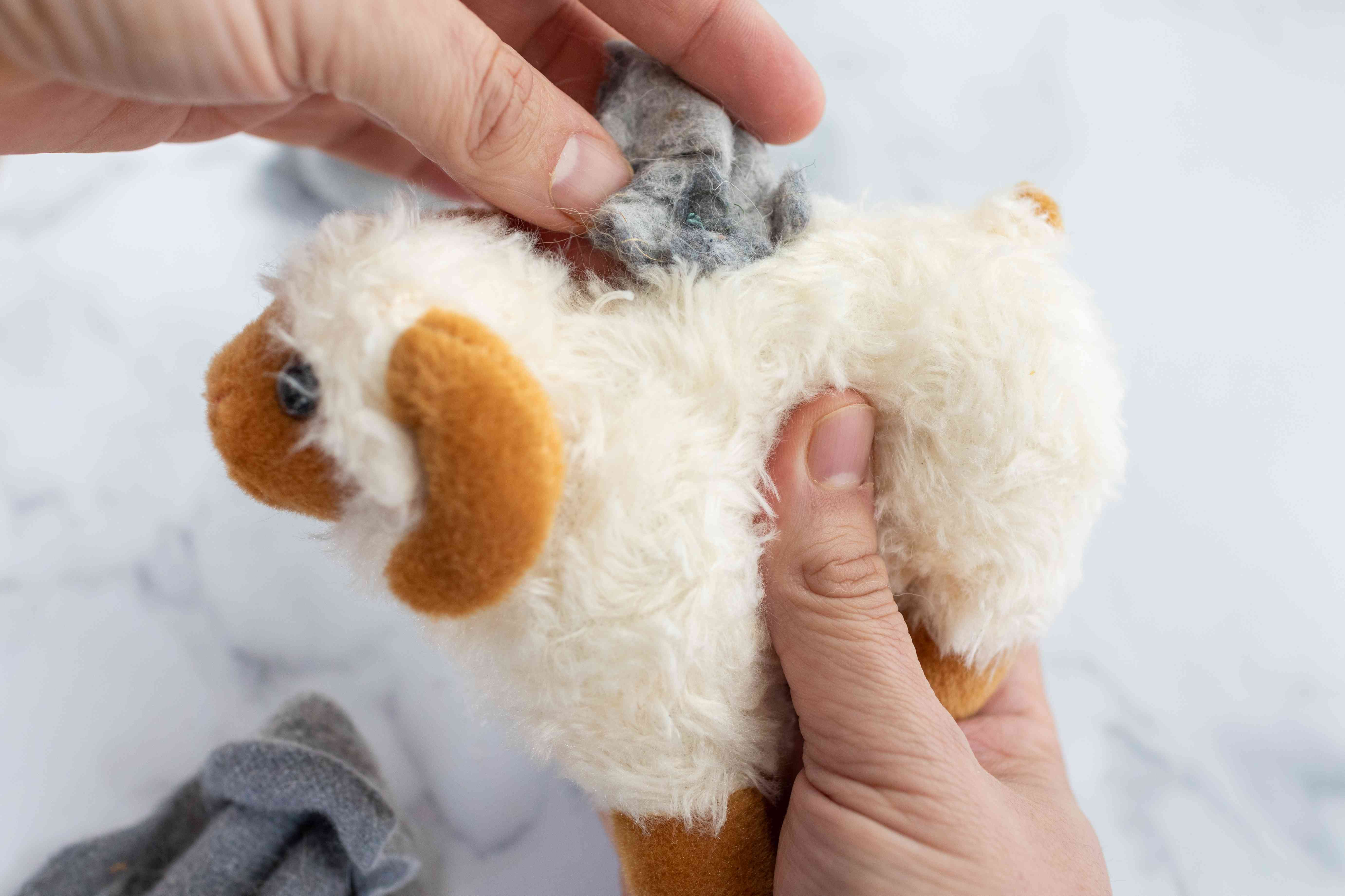 hand stuffs old dryer lint into hole of stuffed animal plush sheep