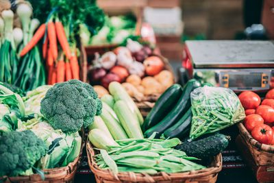 Fresh vegetables, such as carrots, broccoli, peas, and tomatoes in baskets and a food scale
