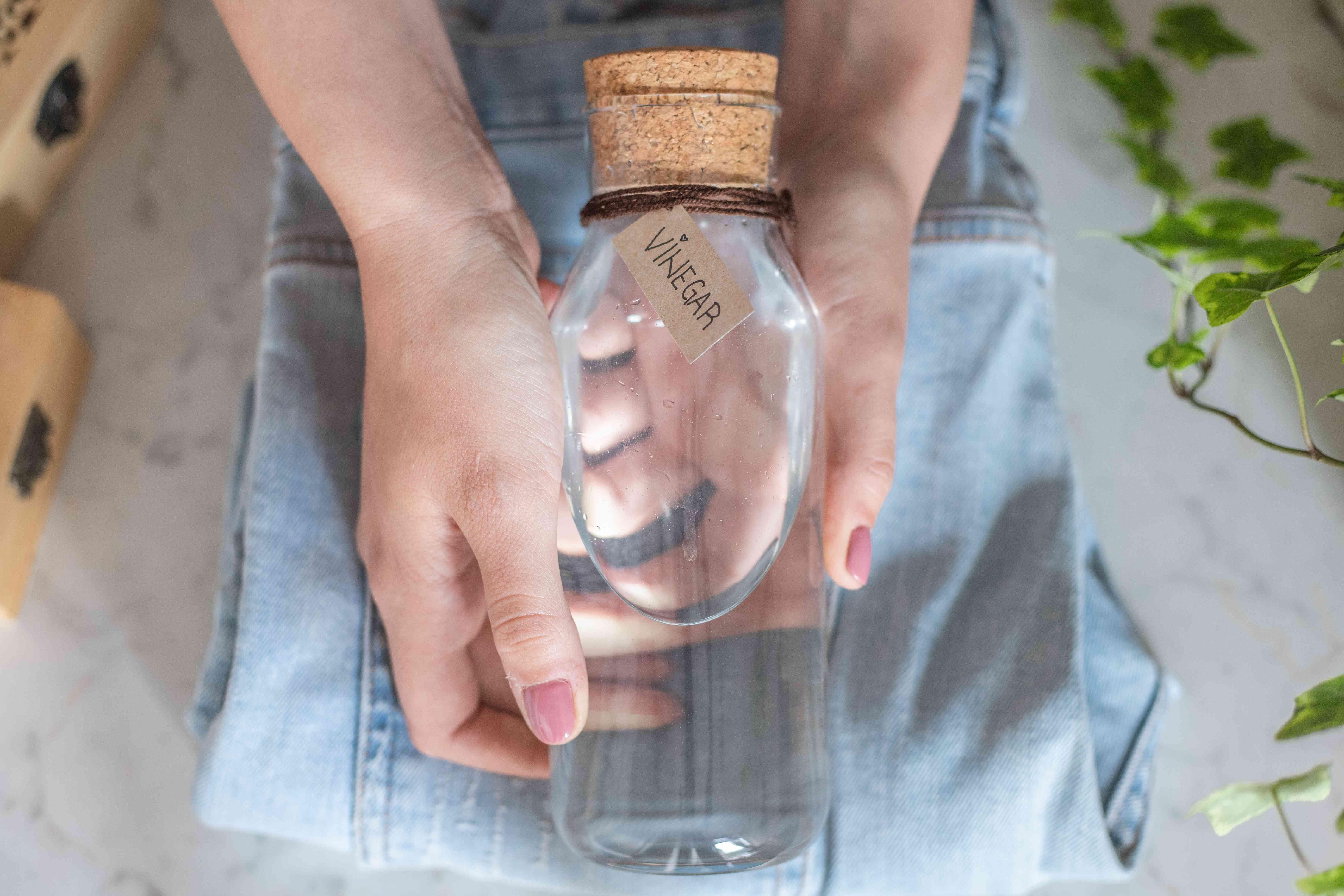 hands hold glass bottle of white vinegar over folded denim clothing