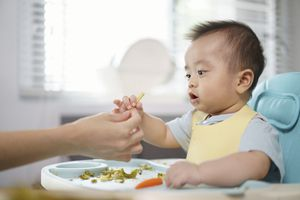 Asian baby grabs veggies from adult hand while sitting in high chair