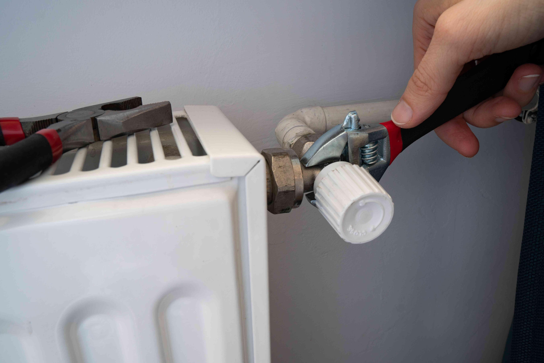 hands use pliers to tighten water leaks near radiator on wall