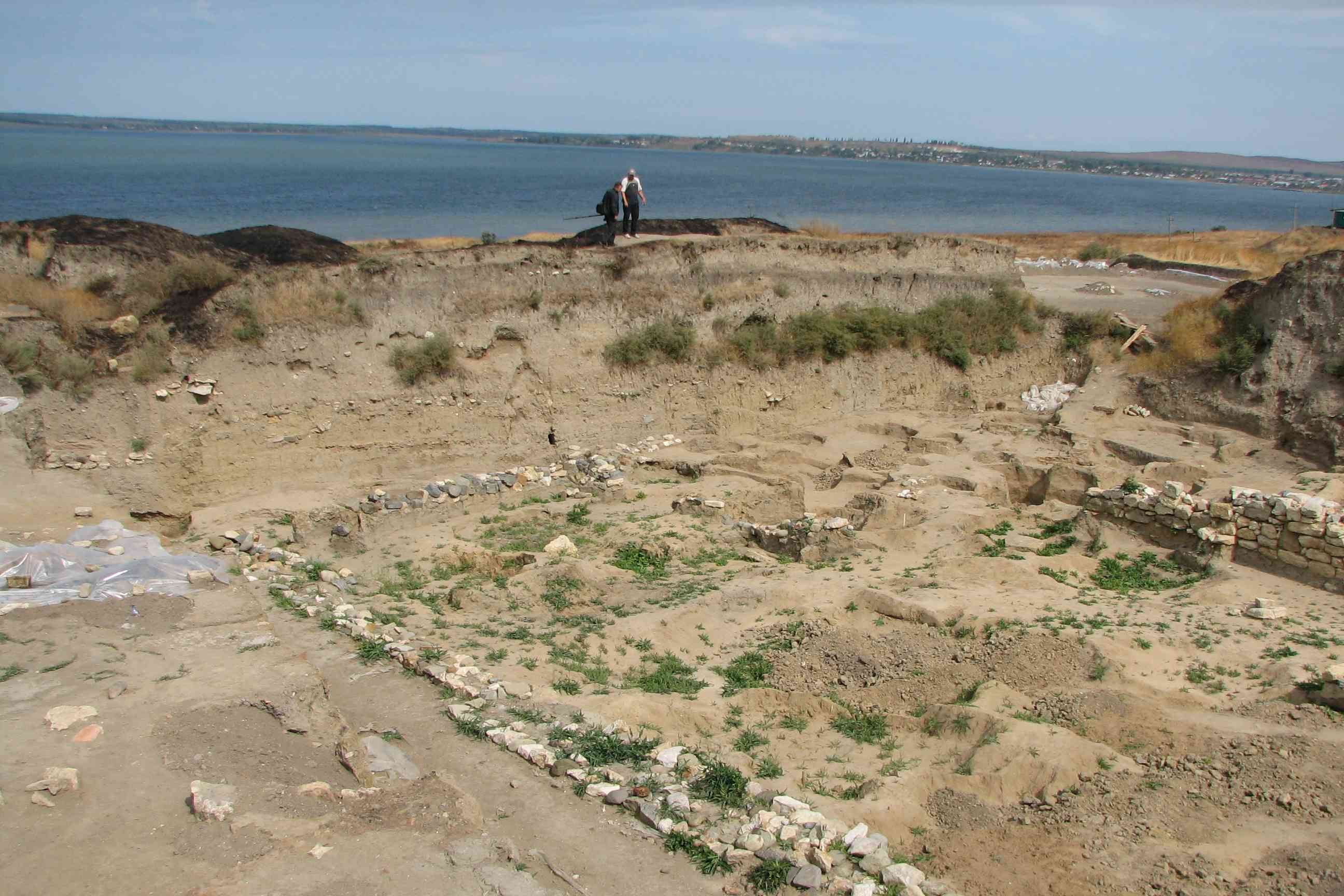 Excavated remains with the sea in the background