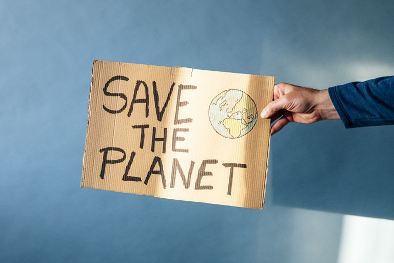 Man's hand holding a cardboard sign that says SAVE THE PLANET