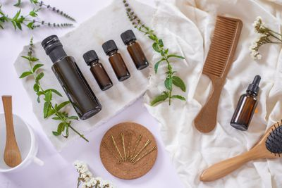 scattered ingredients for olive oil hair mask include oils, combs, spoon, hairbrush