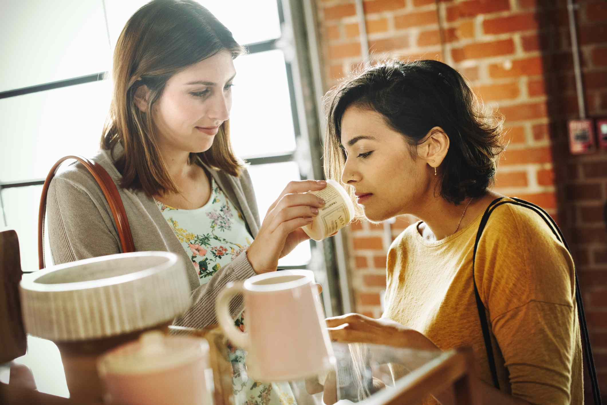 A woman smelling a skincare product with her friend in a shop.