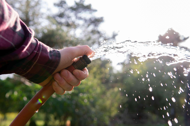 man holds gushing water hose