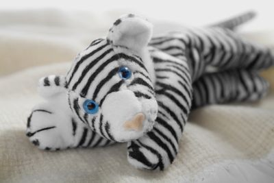Stuffed white tiger toy on a blanket