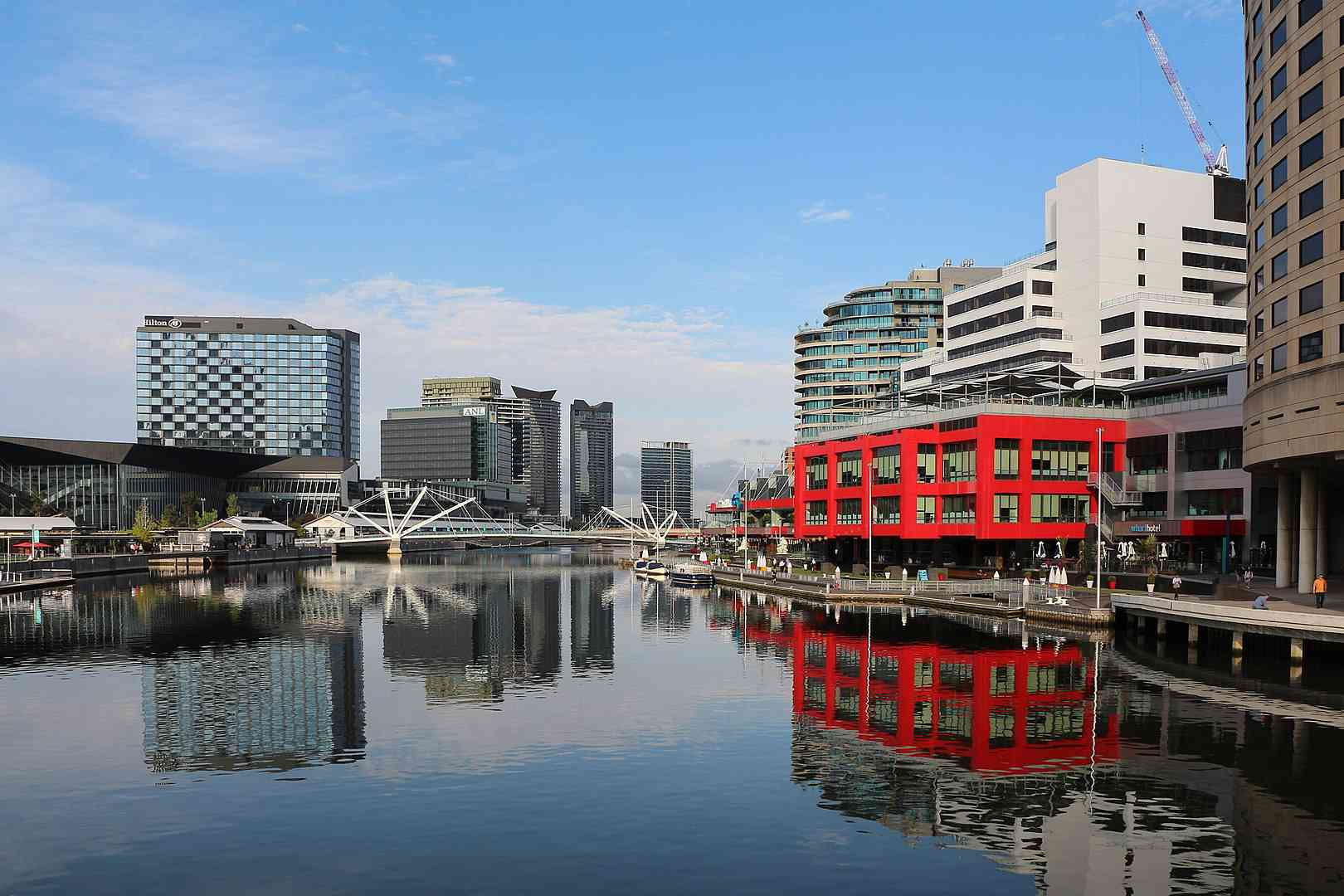 View of the flat Yarra River surrounded by commercial buildings, one framed in red along the riverfront with a blue sky and white clouds above