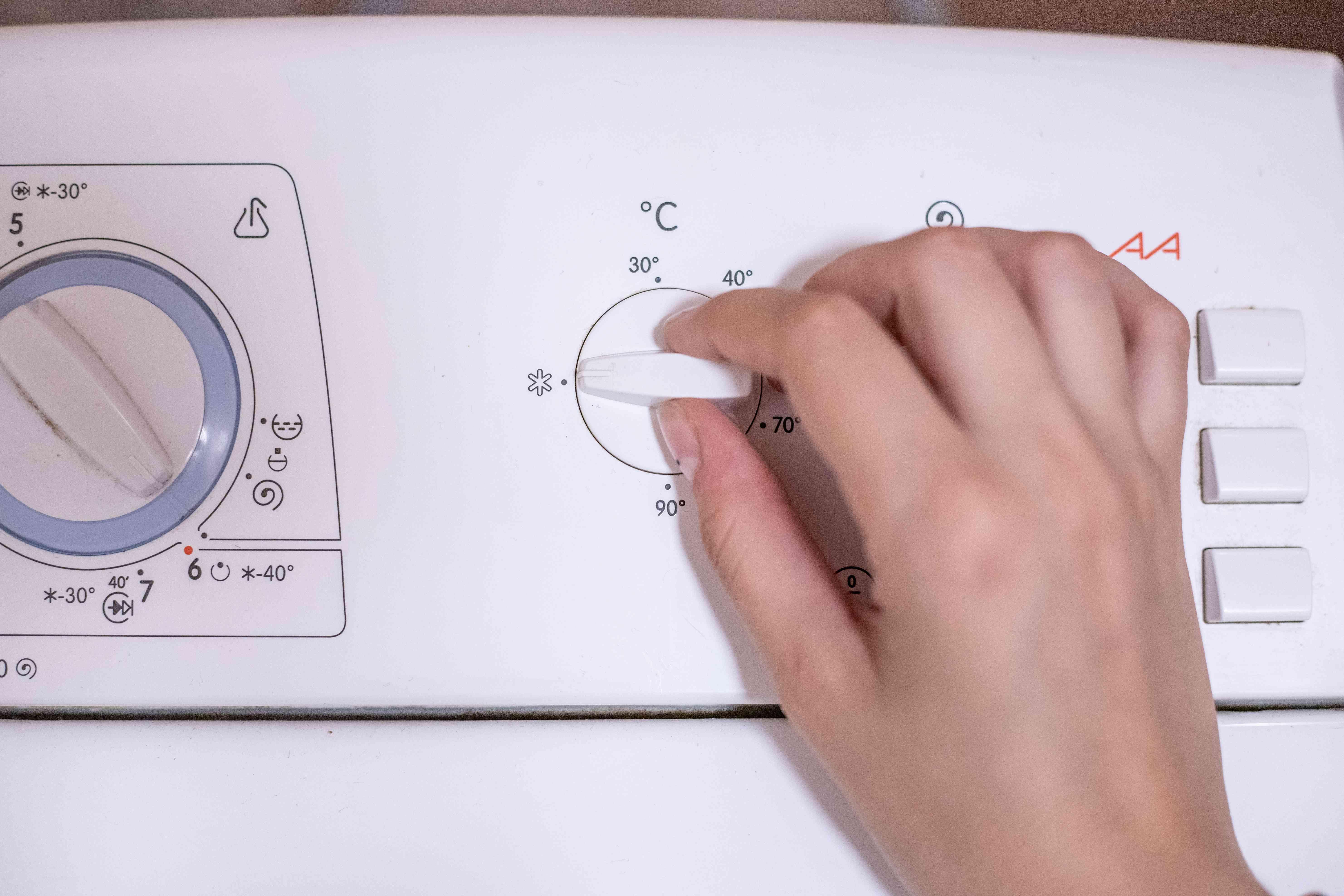 hand changes knob on washing machine to cold water wash