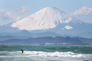 Snow-covered Mount Fuji from a distance behind smaller mountains and surfer in blue-green water