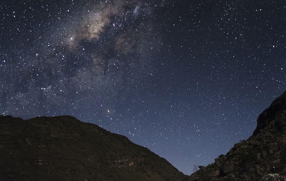 Dark, starry night sky and silhouette of mountain ridge