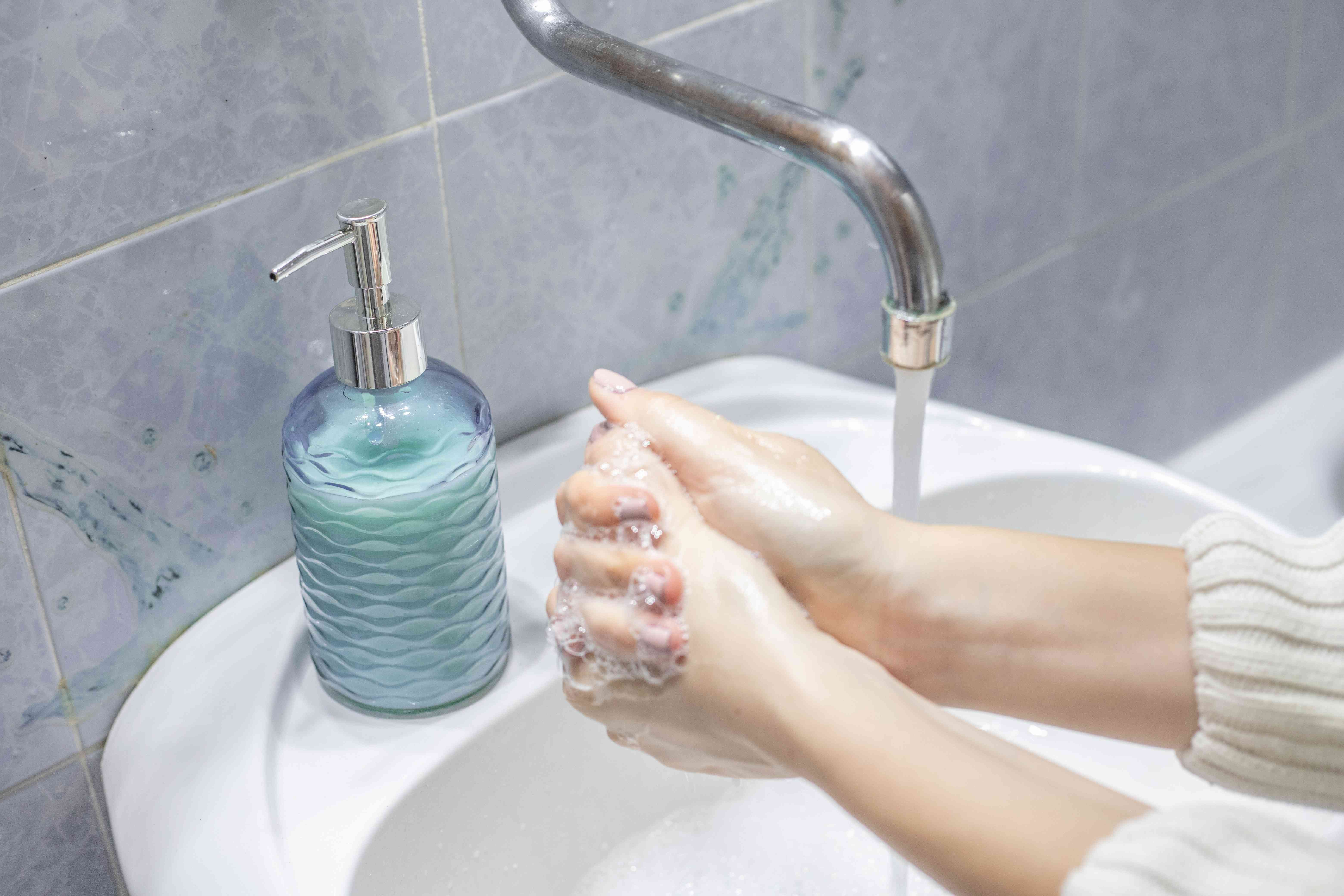 person in sweater washes hands with refillable glass bottle in sink