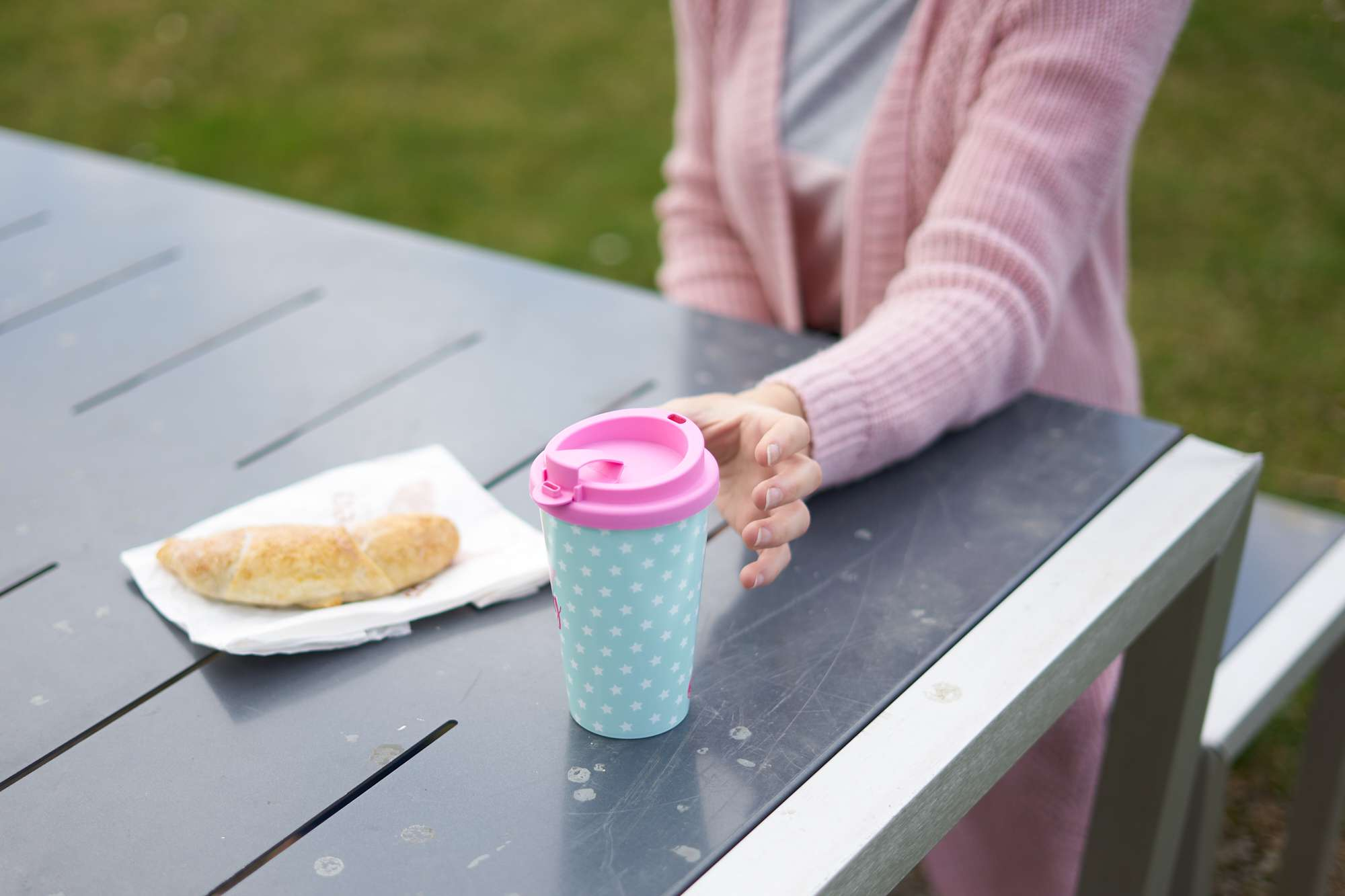 woman in pink cardigan at picnic table reaches for reusable pink and teal coffee cup