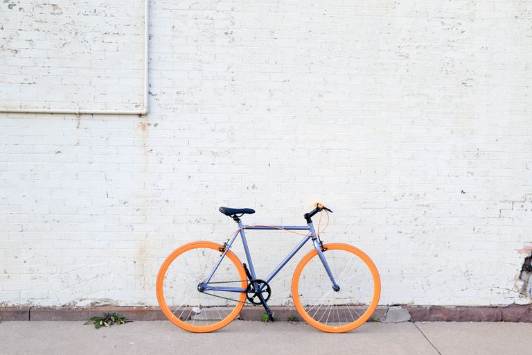 Bicycle with orange tires against a white brick wall