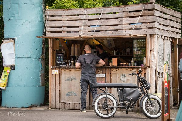 man ordering food or beverage at a stand with his Moke bike nearby