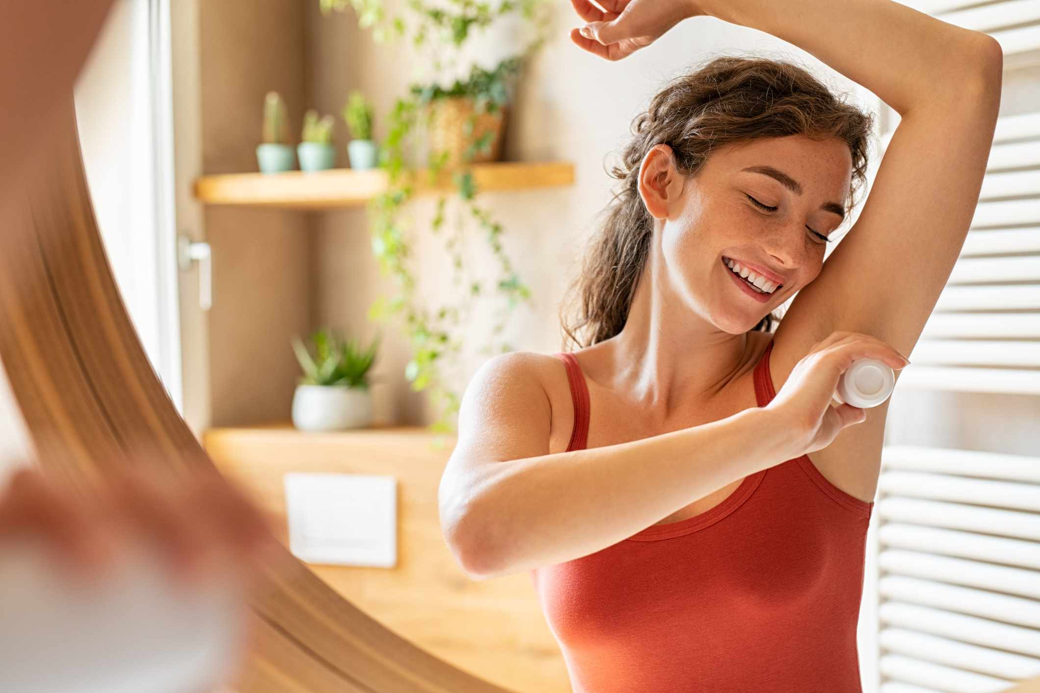 A woman putting on deodorant in a washroom with bright natural light.