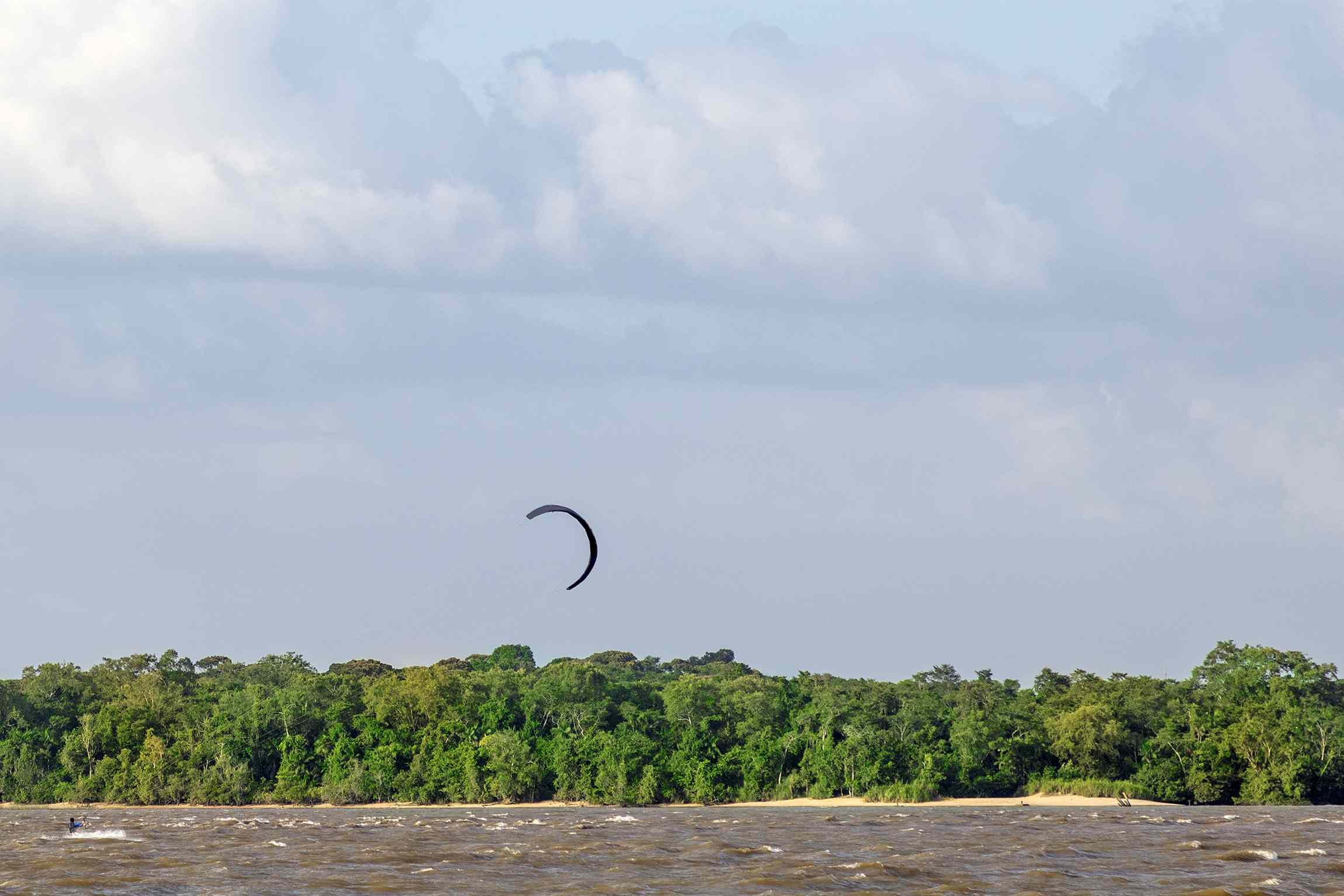 Kite surfer in the dark colored Amazon River with a kite flying above a lush forest of trees under a blue sky with a few white clouds