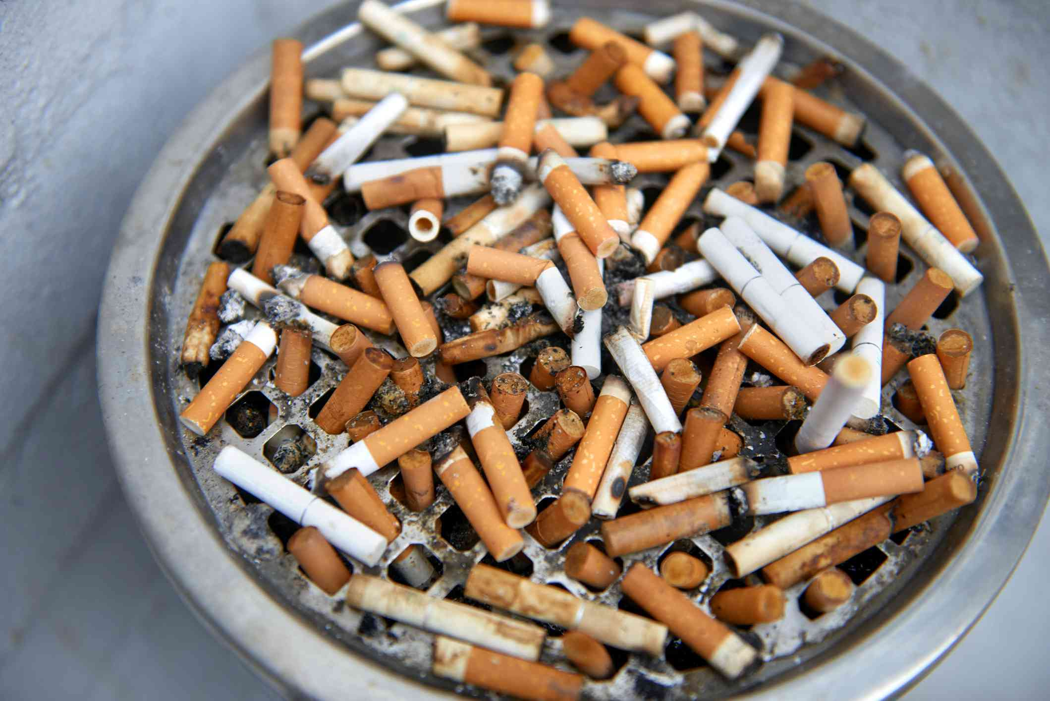 Cigarette ends in an outdoor ashtray outside restaurant