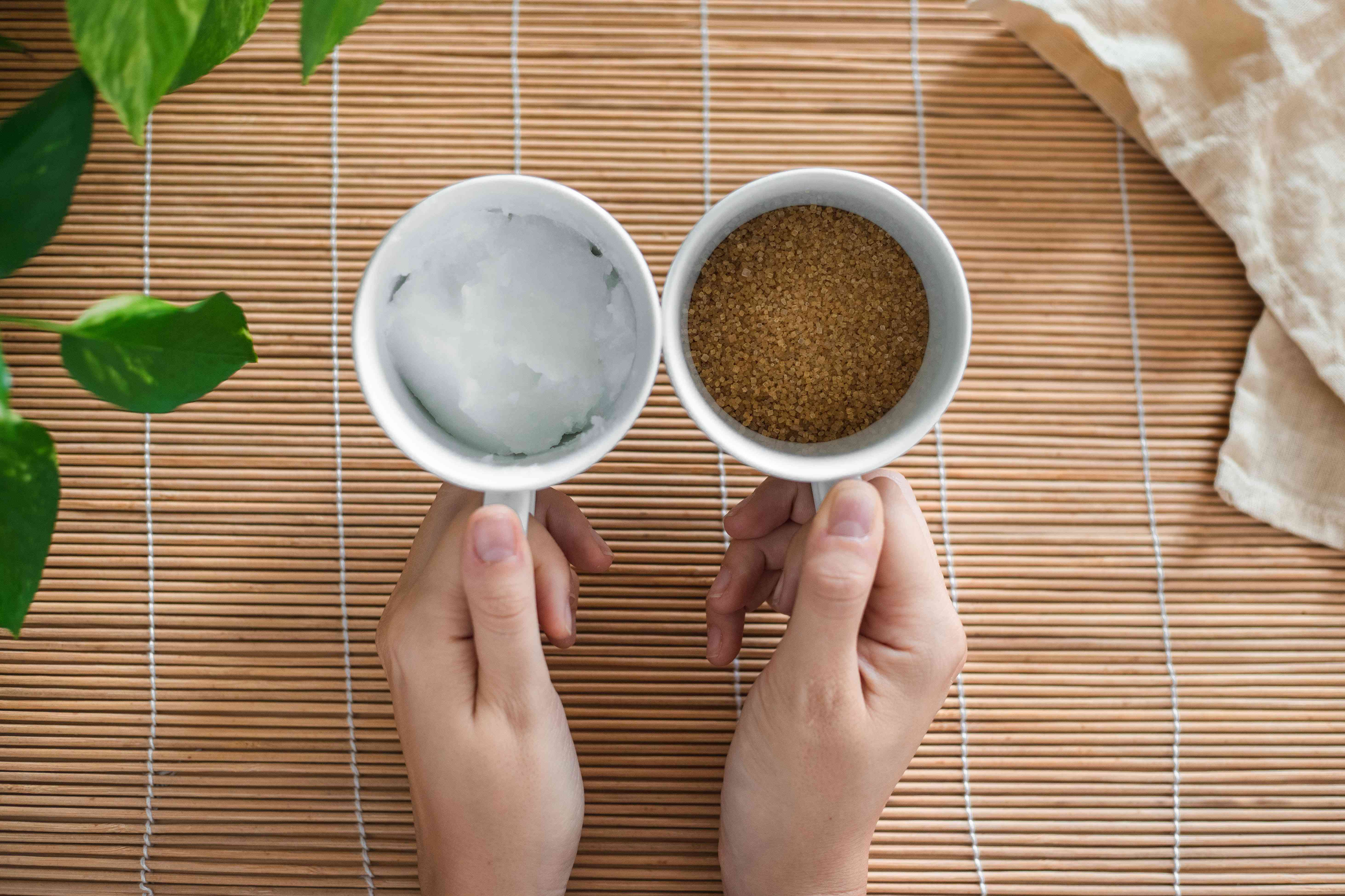 two hands hold coffee cups filled with solid coconut oil and brown sugar to create scrub