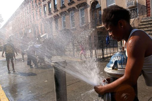 A girl directs the spray from an open fire hydrant as children try to cool off from the summer heat August 7, 2001 in the Brooklyn borough of New York City.