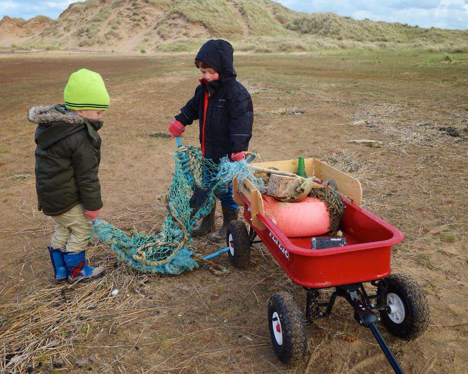 Ollie and Harry clean up litter on the beach.
