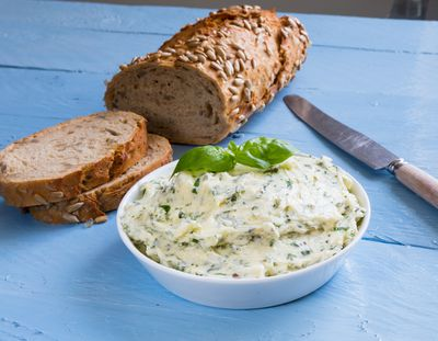 Bowl of butter with herbs and a loaf of brown sunflower bread