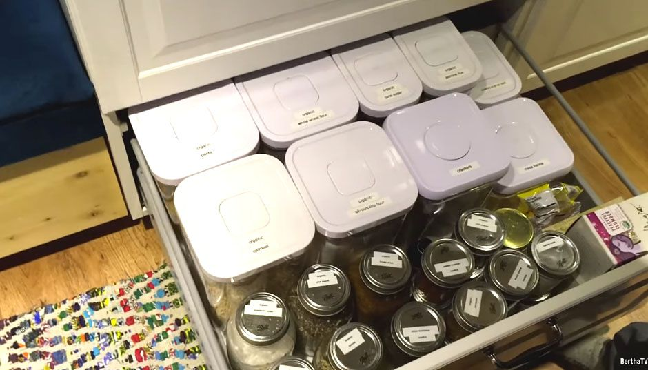 Open drawer with plastic containers and small jars visible