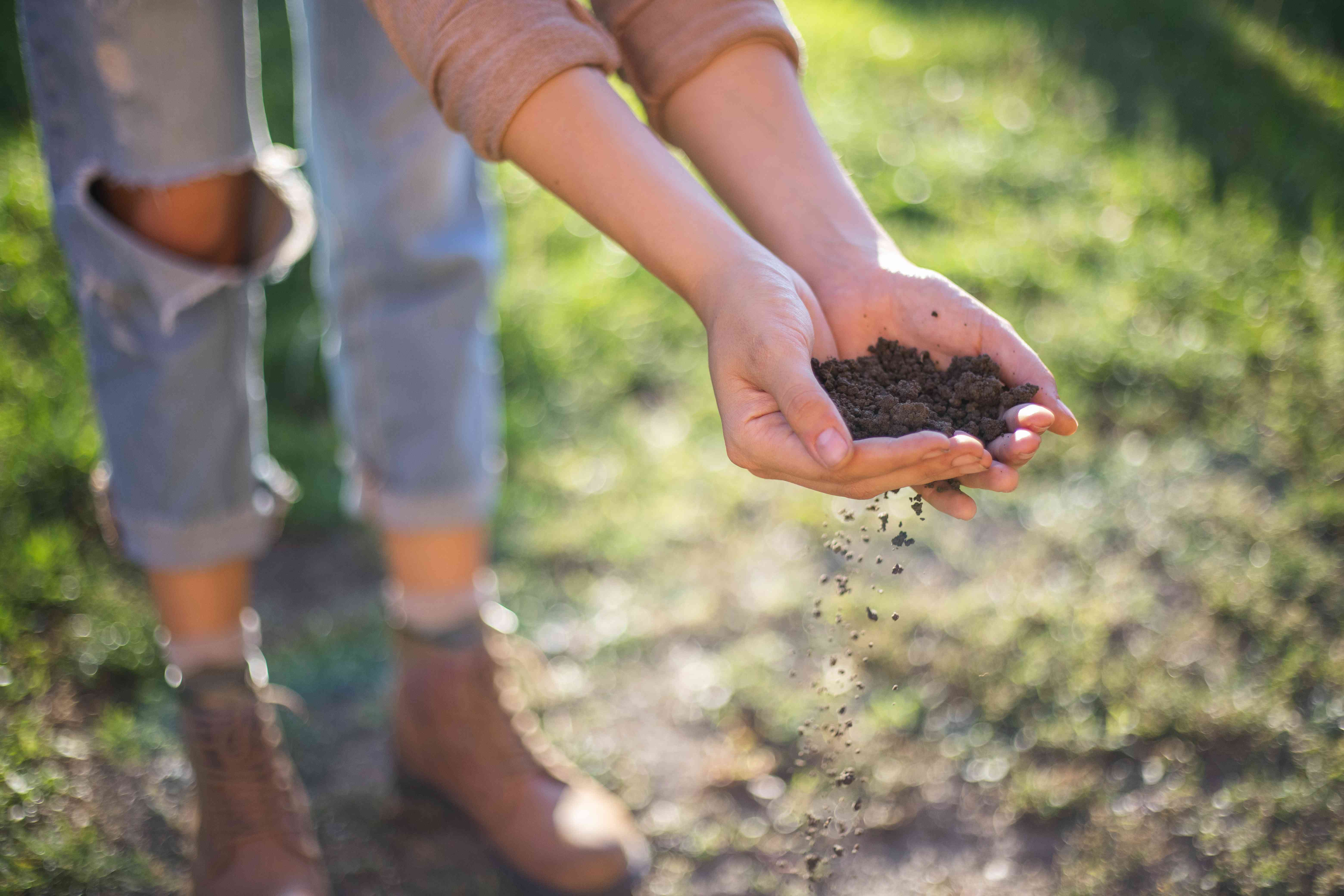 woman in torn jeans holds black compost soil in cupped hands outside