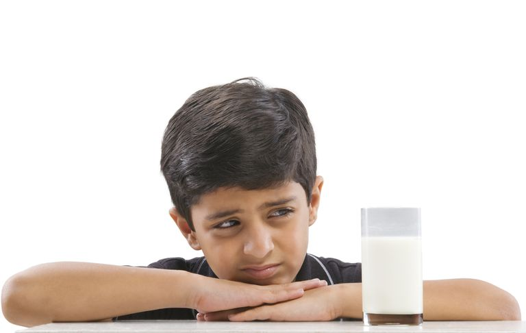 Young boy looking askance at a glass of milk