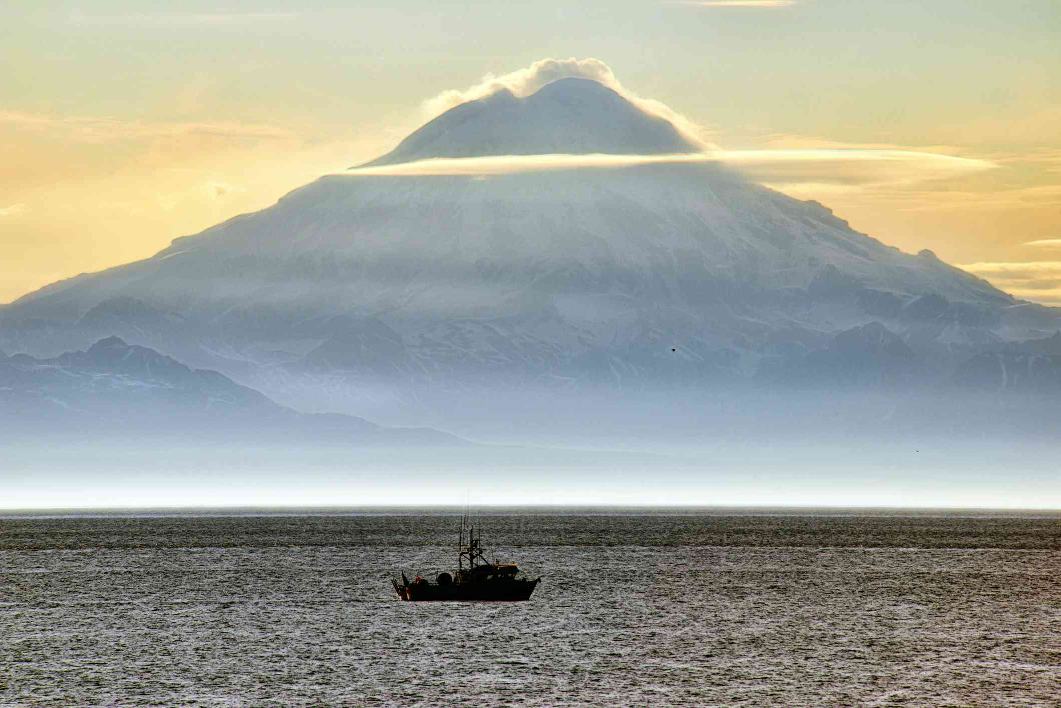 Fishing boat in water in front of Mount Redoubt